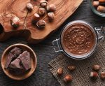 Glass jar with some hazelnut spread, a wooden bowl with milk chocolate, cutting board and nuts on a dark wooden background.